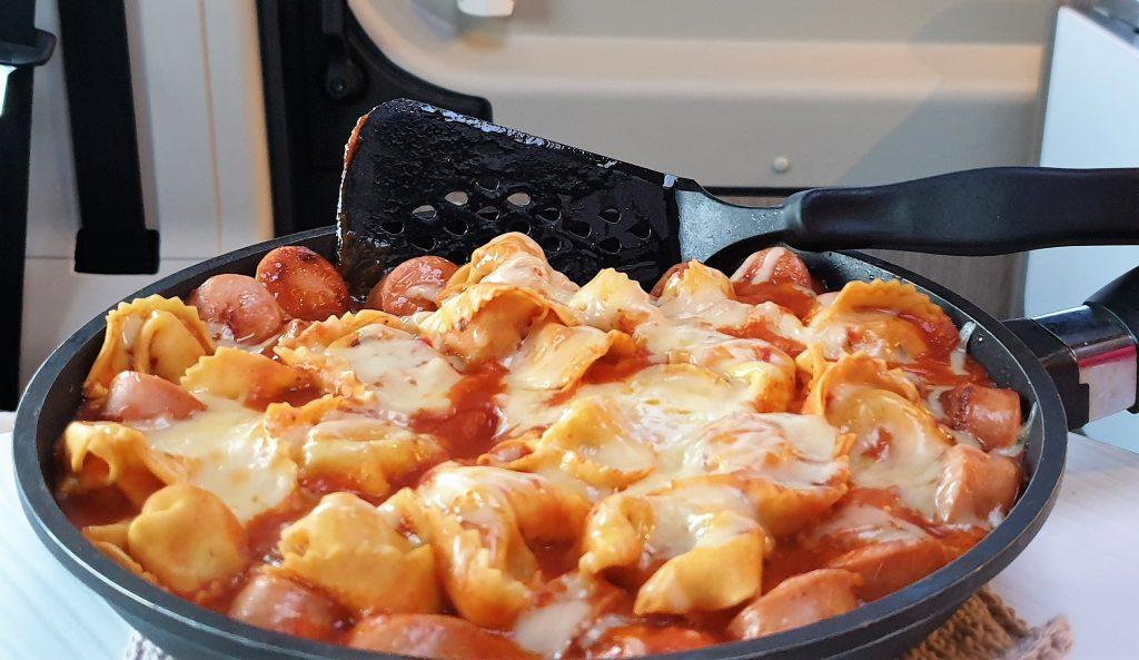 Middag i bobilen - Ostegratinert ravioli med tomatsaus og pølser.
